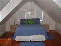 The upstairs master bedroom has a Queen bed and A-frame style ceilings. A great place to escape.