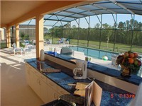 What an amazing pool and summer kitchen, plus a nice lanai area.