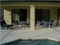 Large covered lanai with loungers and table for enjoying meals or a drink poolside.