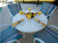 Spacious deck with table and chairs for enjoying your meals outdoors and by the pool.
