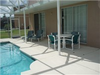 Covered lanai with table and loungers for enjoying meals by the pool or relaxing by the pool with a good book.