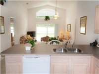 Kitchen overlooks lounge area and pool