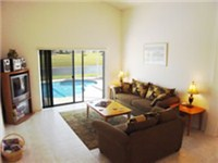 Spacious living room overlooks pool and deck