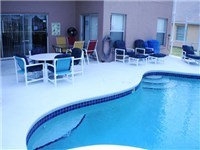 Pool and lanai with plenty of furniture for lounging or enjoying a meal poolside