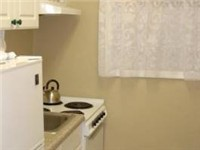 Small Galley Kitchen with Fridge, Stove, Oven and Microwave and stocked with dishes and pans.