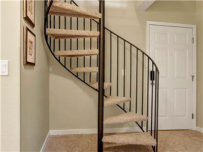 Spiral staircase leads to master suite loft.