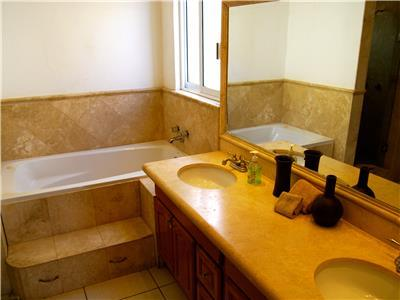 The master bathroom has two sinks and a bathtub