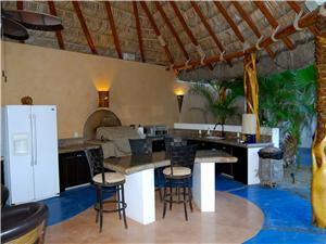 Outdoor BBQ kitchen area under huge palapa