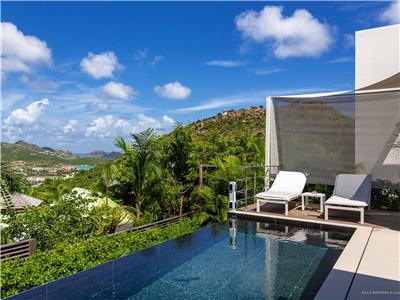 newly built Villa overlooks a landscape of green rolling hills, palms, orange flamboyant trees and o