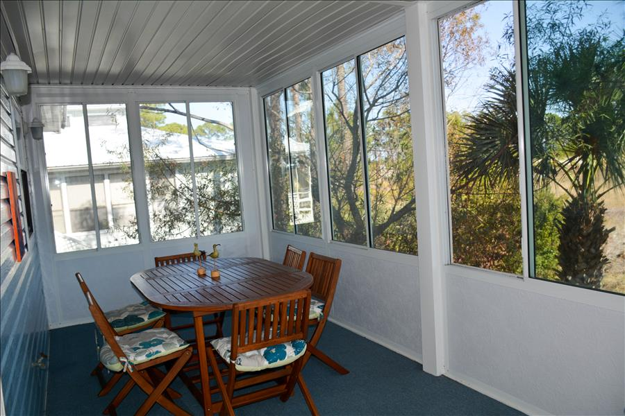 Glass enclosed porch with outside dining table.